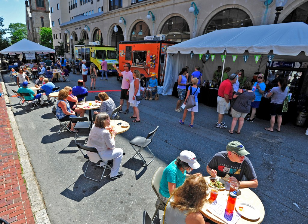 People enjoy the food trucks lined up outside the Zeiterion during the New Bedford Folk Festival.