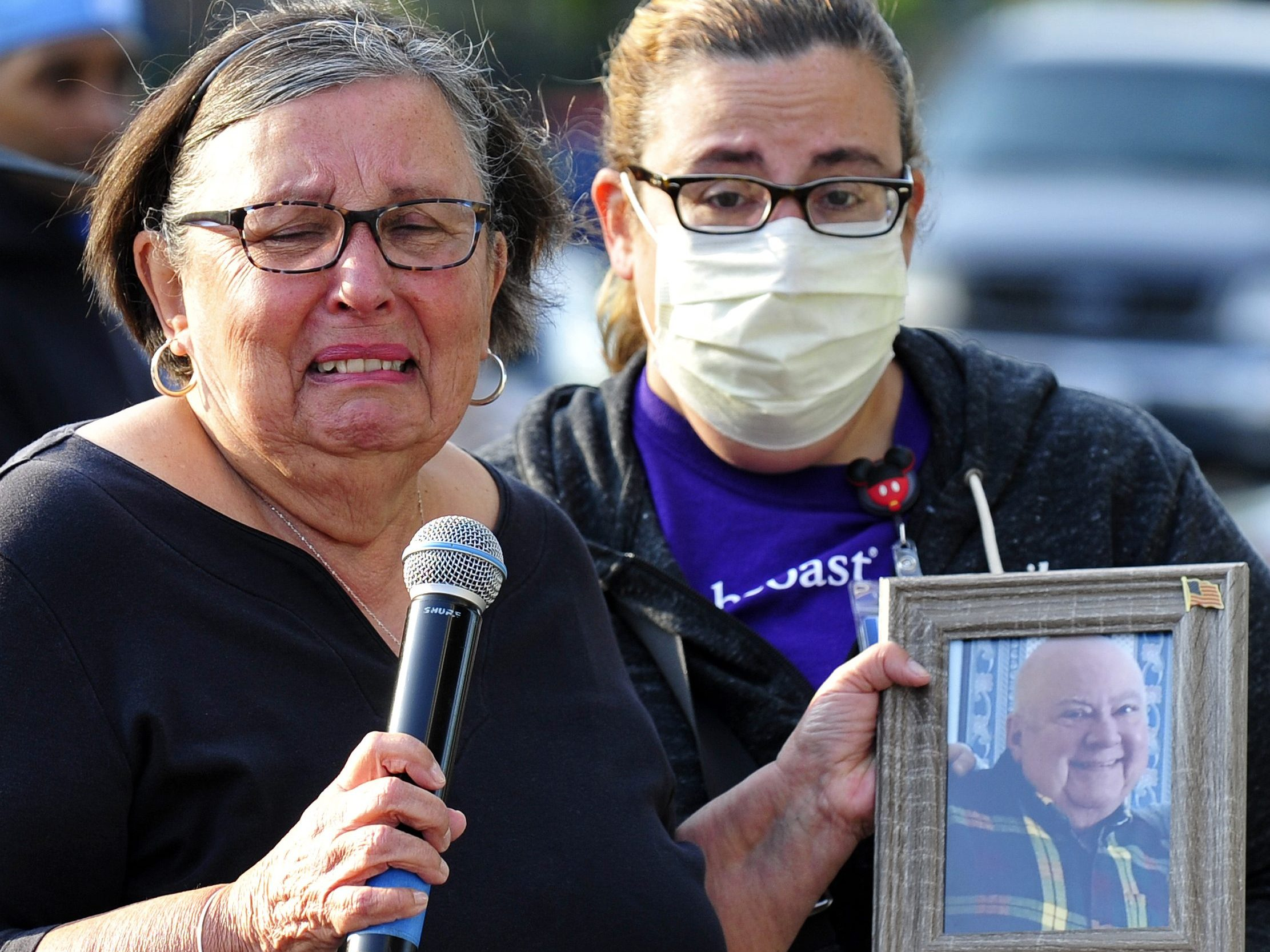 Ida Souza holds photo of husband at Monte Park COVID memorial service.