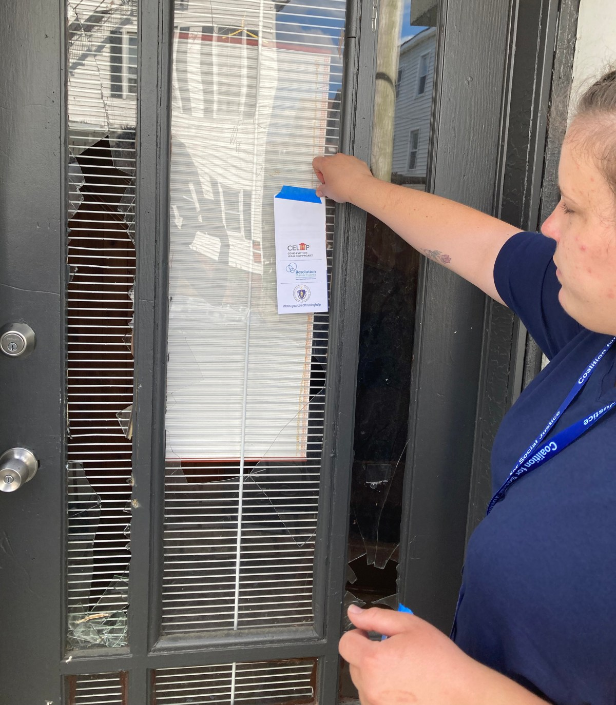 Sigute Meilus, with the Coalition for Social Justice, posts information for legal services and rental relief on the door of a tenant facing eviction.