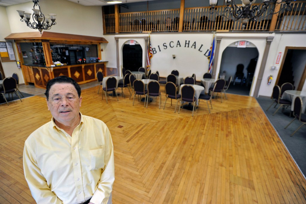 Gabriel DeRosa stands in the empty banquet hall at the Bisca Club.