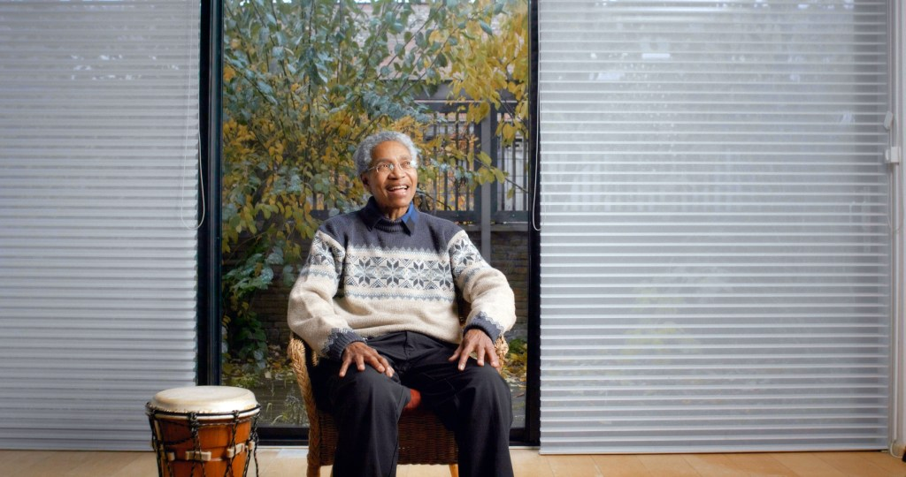 Beverly Glenn-Copeland seated in front of a large window next to a drum.