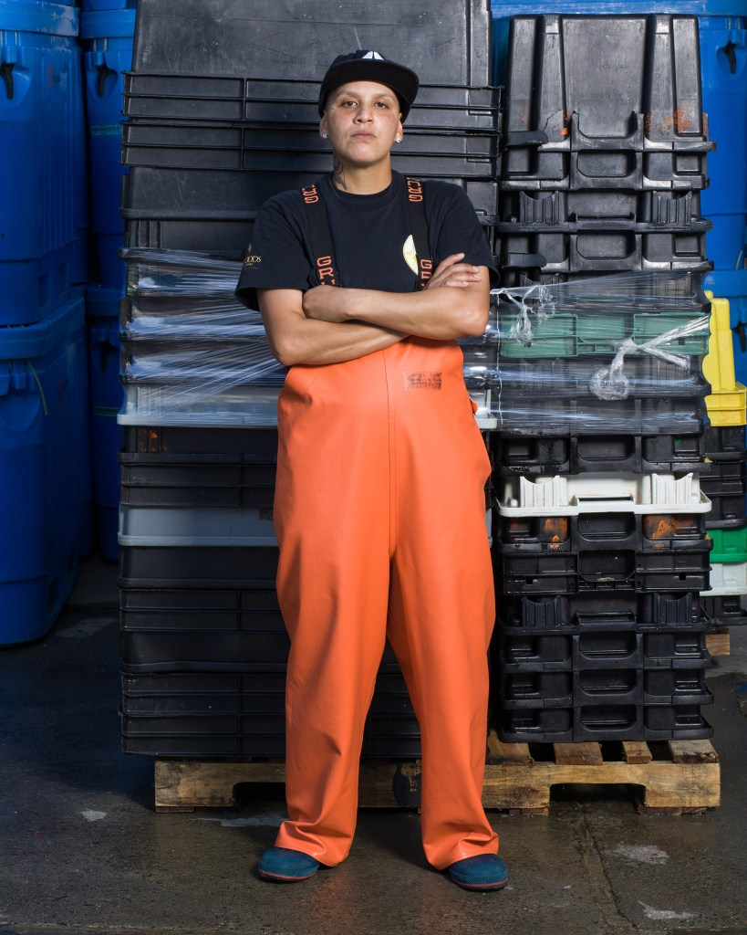 Seafood plant worker poses with arm crossed.