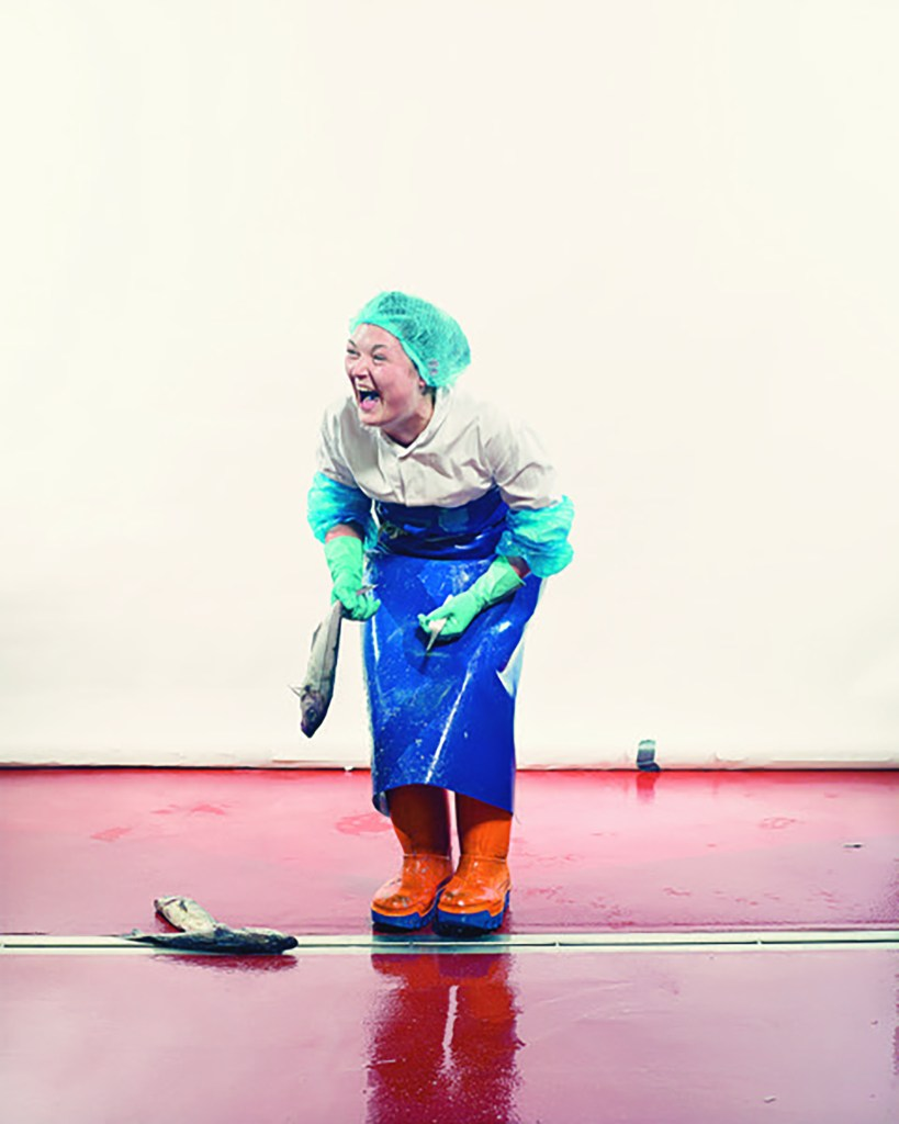 Scottish filleter Louise Hutchins, bent over laughing with a fish in one hand and knife in the other.