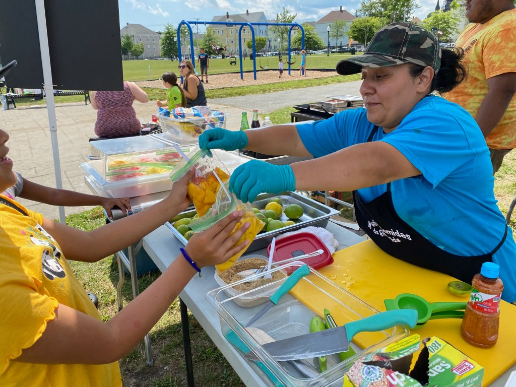 Edith Diego serves fresh mango with lime and Tajin at Riverside Park in New Bedford.