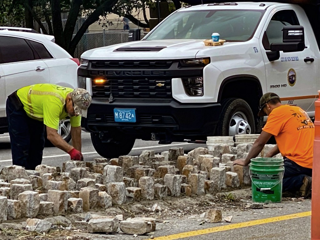 Workers install Belgian blocks at busy downtown New Bedford intersection.