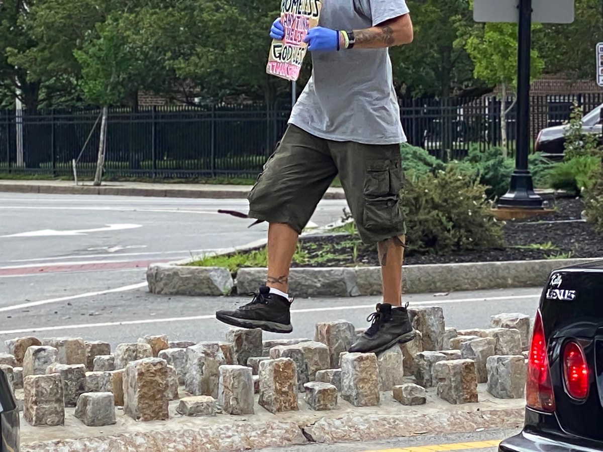 """A panhandler navigates the cobblestones recently redesigned so they are pointing upward at """"the octopus"""" intersection downtown."""